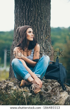girl sitting on the big stone near the tree
