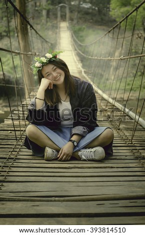 Girl sitting on the bridge during the summer holiday period.