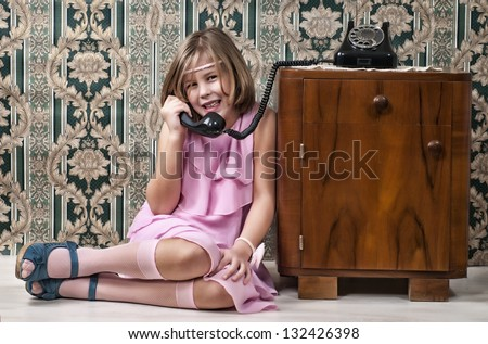 Girl sitting on the floor and make phone calls - stock photo