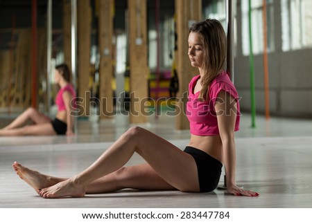 Girl sitting on the floor in pole dance class - stock photo