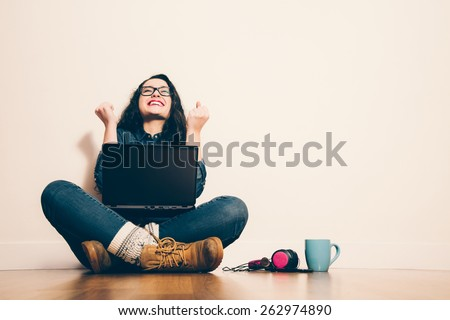 Girl sitting on the floor with a laptop raising his arms with a look of success - stock photo