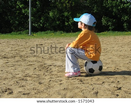 girl sitting on the football - stock photo
