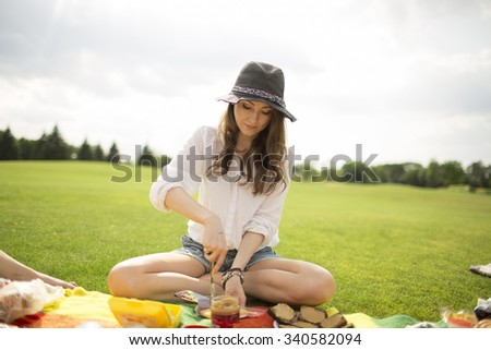 girl sitting on the grass and making sandwiches - stock photo