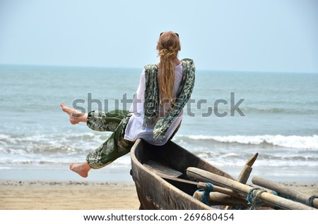 Girl sitting on the old fishing boat. Rajbag beach of South Goa, India - stock photo
