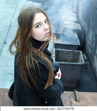 Girl sitting on the roof of the garage on the background of a burning dumpster