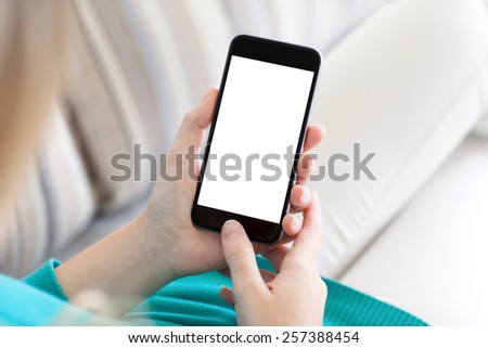 girl sitting on the sofa and holding a phone with isolated screen