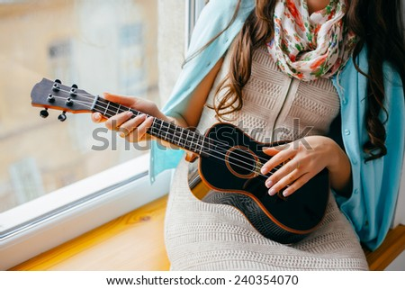 girl sitting on the window. playing guitar - stock photo