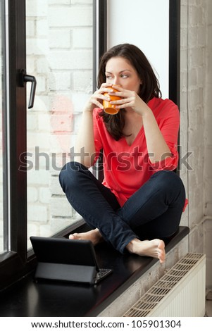 Girl sitting on windowsill with cup of tee and notebook - stock photo