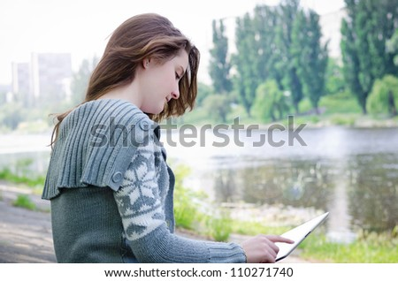 Girl sitting outdoors on a paved driveway in a riverbank using a touchscreen tablet