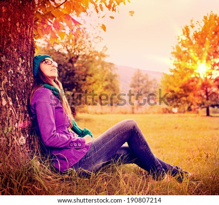 girl sitting under a tree in sunset - stock photo