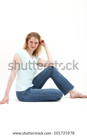 Girl sitting up straight but comfortable on the floor leaning her elbow on a knee.