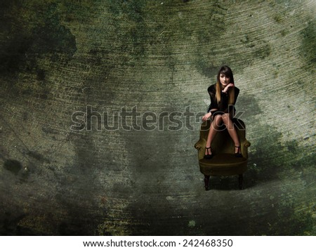 girl sitting with foot on green sofa - stock photo