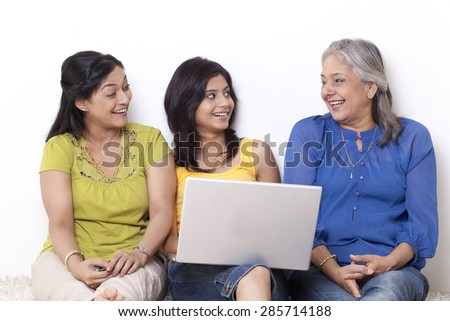 Girl sitting with her mother and grandmother shopping online - stock photo