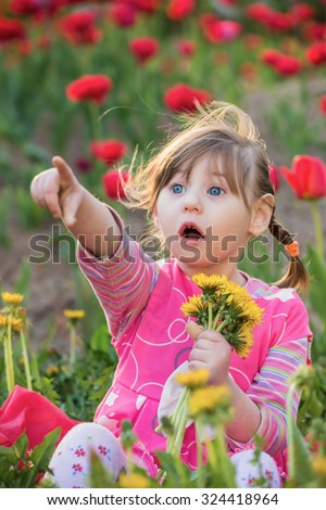 Girl sitting with the dandelions - stock photo
