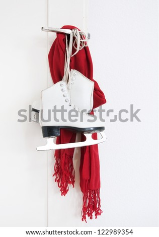 Girl skates and red scarf hanging on the door - stock photo