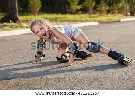 Girl skating outdoors. Child on roller skates fall. Injury