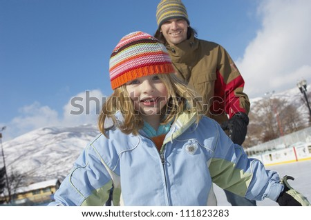 Girl skiing with father standing in the background