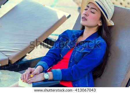Girl sleep on the Beds by the pool with book