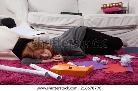 Girl sleeping among notes on the floor - stock photo
