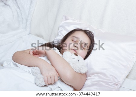 Girl sleeping on the back with a toy