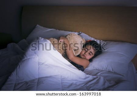 Girl sleeping on the bed with a teddy bear - stock photo