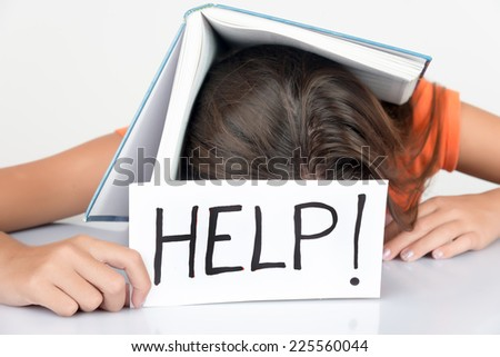 Girl sleeping with a textbook over her head and holding a sign with the word Help! - stock photo