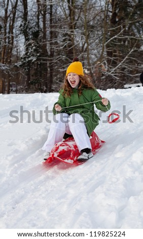 Girl slides down hill on red plastic sledge in a snowy winter park - stock photo
