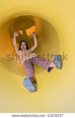 girl sliding in a yellow tube slide in a playground