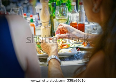 Girl slips with his hands a crustacean of his shrimp dish