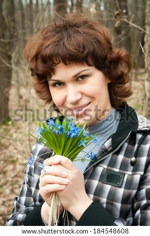 girl smelling aroma of snowdrops in the forest - stock photo