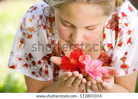 Girl smelling hibiscus flowers while sitting on a green grass garden, close up. - stock photo