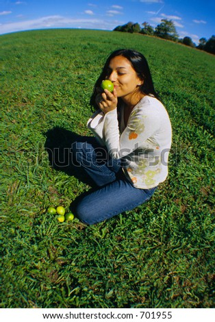 Girl smelling limes on a grass field. - stock photo