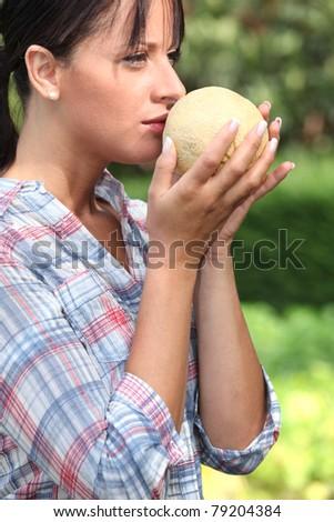 Girl smelling melon - stock photo
