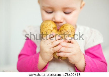 girl smelling potato in hands