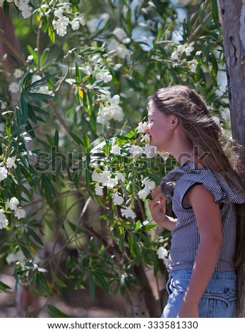 Girl smelling the flowers (rhododendron) in the garden - stock photo