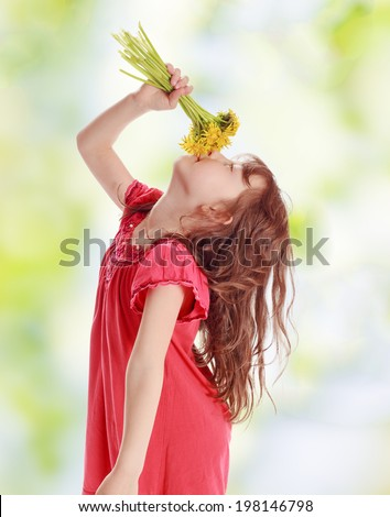 Girl smells a bouquet of yellow flowers - stock photo