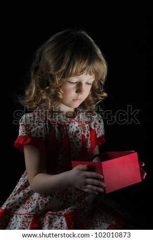 Girl smiles and holding a gift in magic packing on a black background