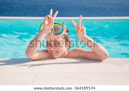 girl smiling and wearing a mask swim in the pool - stock photo