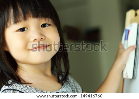 Girl smiling at camera while erasing the drawing board - stock photo
