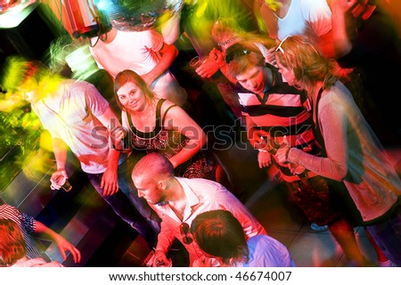 Girl smiling at the camera on a busy dance floor in a discotheque - stock photo