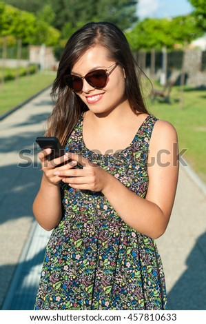 Girl smiling standing and texting on telephone outside in park in sunlight