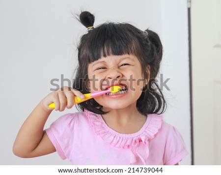 girl smiling while brushing her teeth - stock photo