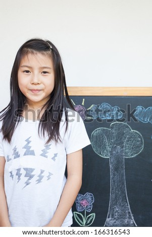 girl smiling with blackboard drawing