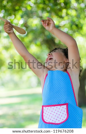 girl smiling with wooden spoon - stock photo