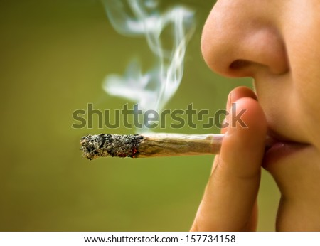 girl smoking marijuana close up - stock photo