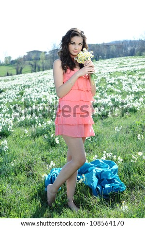girl sniffs flowers that collected - stock photo