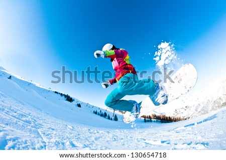 girl snowboarder having a great time jumping - stock photo