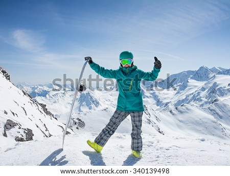 Girl snowboarder on the background of high snow-capped Alps in sun day, Austria