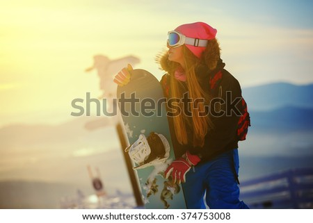 girl snowboarding in the mountains at sunset time - stock photo