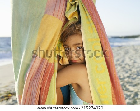 Girl (5-7) snuggling up to mother wrapped in large towel on sandy beach, smiling, close-up, side view, portrait